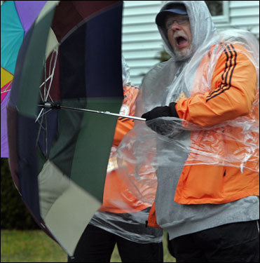 Ed Mills, a volunteer from Hopkinton, said ' I feel like Mary Poppins' when the wind kept blowing his umbrella inside out. Mills was at the Hopkinton Church driveway, keeping people away from the elite runners.