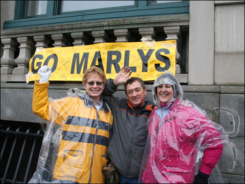 (Left to right) Tawnia Newell, Tom Plett, and Julie Vosbergh put up this bright sign in Kenmore Square. 'Go Marlys,' refers to Plett's wife, Marlys. The couple is from Hillsboro, Kansas.
