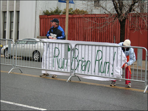 This sign refers to Brian Watson, of Lucan, Ontario. Two members of his running group there, Jennifer and Bruce Lamb (pictured) drove down to cheer him on. They anchored the sign to the barricades, as strong winds tossed around other signs and balloons. 'He's the speed demon' of our running group, Jennifer Lamb said of Watson.