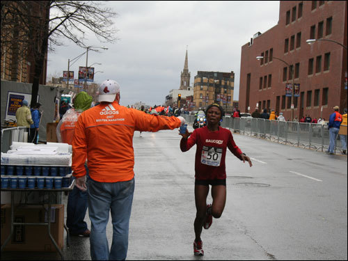Hand off: The first runners passing through Kenmore Square eagerly grab water from the race volunteers.