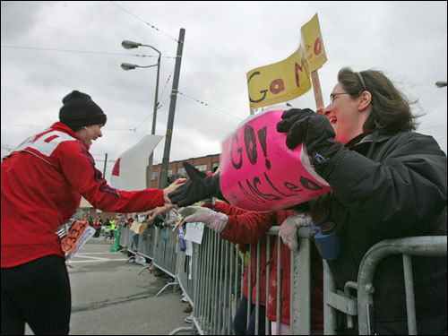 At Cleveland Circle, first-grade teacher Jane Leo (left) greeted students and their parents including Sharon Shoffmann (right) of Brookline, as they cheered her on during the marathon.