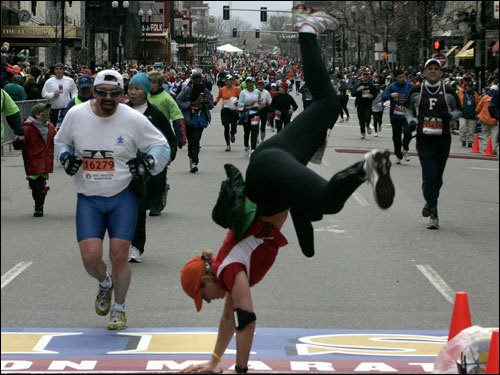 A runner does a cartwheel at the finish line of the Boston Marathon.