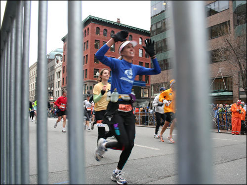 A runner raises her arms near the finish line.