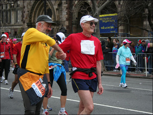 Two runners shake hands after crossing the finish line.