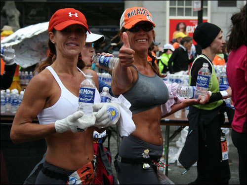 A runner gives a thumbs up near the finish line.