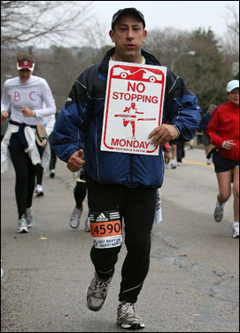 Reza Olla of Boxford carries a 'No Stopping' street sign as he makes his way up Heartbreak Hill.