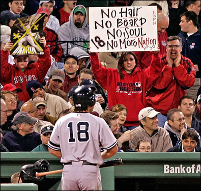 Johnny Damon walked to the dugout after striking out, while a fan held up a sign directed at the former Sox center fielder.