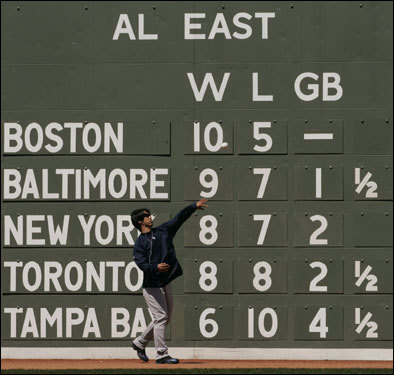 Yankees pitcher Kei Igawa worked out in the outfield in front of the AL East standings posted on the Green Monster.