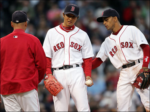 Sox shortstop Julio Lugo (right) congratulated Hideki Okajima (center) after Okajima got the first out of the eighth inning before being taken out by Terry Francona (left).