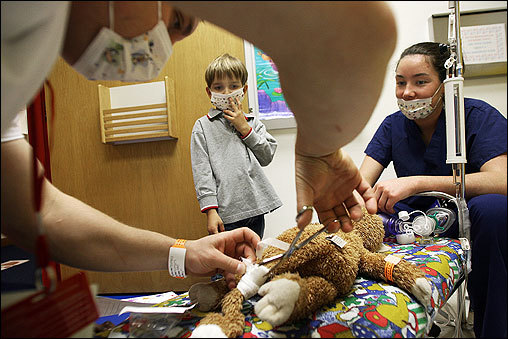 Nicholas Caliri, 4, watched as nursing student Darrell Bormann (left) performed surgery on his stuffed monkey, 'Oo-ah,' Tuesday morning at the Shriners Hospital for Children in Boston. Students from the Boston Children's School visited the hospital for the 25th year of a program in which hospital staff members showed them how they care for patients.