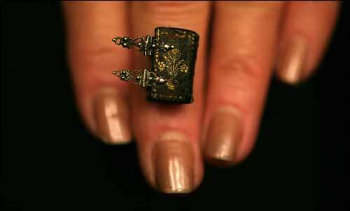 Rare-book dealer Anne C. Bromer balanced 'Little Flower Garden,' 13 by 9 millimeters, on her finger. The book will be showed at Boston Public Library's 'Miniature Books: 4,000 Years of Tiny Treasures,' which opens tomorrow.