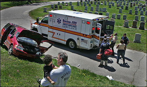A woman and her toddler were treated by Boston paramedics Monday after she lost control of her van and rolled into the Mount Hope Cemetery in Mattapan. George Cahoon, a lieutenant with the Boston Fire Department, held the toddler as paramedics moved the driver into the ambulance.
