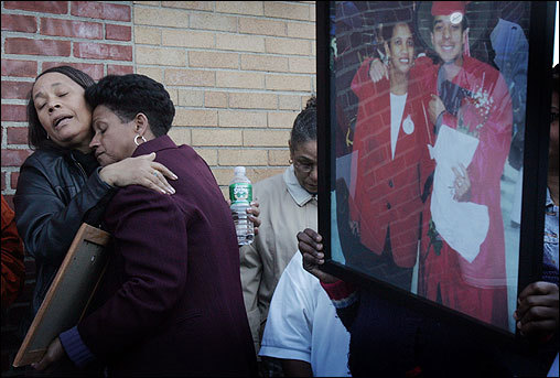 Domingas Carvahlo (left), who lost three nephews to violence and whose son was paralyzed by a bullet, received a hug from Isaura Mendes during a peace vigil Sunday evening at the corner of Wendover and Dudley streets.