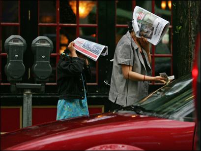 An unidentified woman and a child sought shelter under newspapers as she searched for her car keys near North Station today. (Matthew J. Lee/Globe Staff Photo)