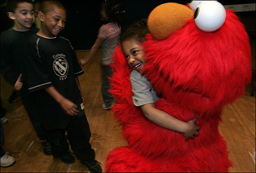 Students from the William Blackstone Elementary School on Shawmut Avenue in Boston received a visit from Elmo after being awarded 'The Good Neighbor Award' from Sesame Place, the theme park based on Sesame Street. The award was created to recognize schools that demonstrate acts of good citizenship. This year students took part in a recycling campaign and collected about 8,000 pounds of paper and old newspapers. The students greeting Elmo are (from left) Juan Lopez, Jhonniel Guereva, and Emely Soto.
