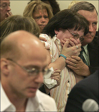 While Rod Matthews (foreground) testified at his second parole board hearing, Jeanne Quinn (background) reacted to his testimony. Matthews was convicted of second degree murder in the beating death of Shaun Ouillette, Jeanne's son, in 1986. At right is Jeanne's husband, Paul Quinn.   Story