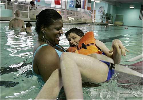 At the Fernald Development Center, Joan Hanlon, foreground, and her twin sister, Jean, in the background, have their much-loved time in the pool.