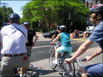 As bikers ride through the crowded Boston streets, Urban AdvenTours tour guides help to block intersection traffic so that bikers have a free area to cross. Tour guide Mike Maker (front) says that this helps to put bikers at ease.