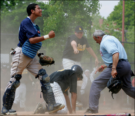 Boston English High School's catcher Jhoneris Mendez (left) gestured after tagging Boston Latin Academy's John Adames (center) out at home plate, during Monday's city baseball championship game.