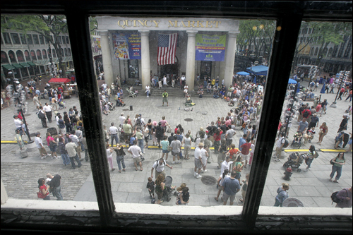 Peter Panic (in green, upper center) of Cambridge entertained a crowd during the Street Performers Celebration Festival at Faneuil Hall on Monady, May 28.