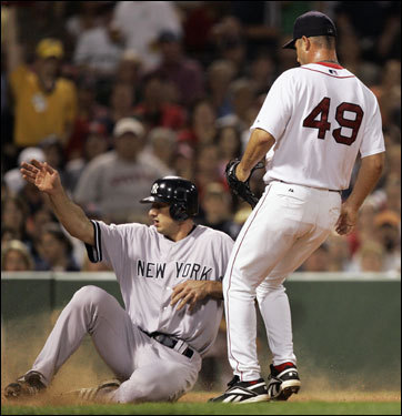 Yankees first baseman Josh Phelps (left) slid into home safely while Red Sox pitcher Tim Wakefield (49) waited for a late throw in the fourth inning.