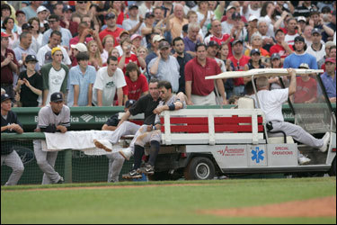 Fans watched as Doug Mientkiewicz was carted off the field Saturday. Many applauded for the former Red Sox first baseman.
