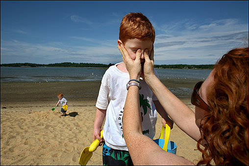 Jennifer Greenleaf cleared sand from the eyes of her 4-year-old son Benjamin Prenderville as her 18-month-old son Timothy Prenderville worked on a sand castle Monday at the Hingham Bathing Beach. The boys were apparently slow to learn that tossing up sand in a breeze would make it blow into one's eyes.
