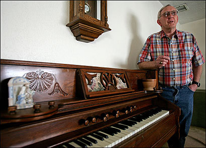 Mike Romney, Mitt Romney's cousin, in his living room in Colonia Juarez, Mexico, leaning on an organ that was brought to the town through the insistence of Hannah Hood Hill Romney, who was the great-grandmother of both Mike and Mitt Romney.