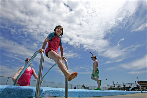 Cecilia Viveiros, 9, enjoyed the first opening day at the Marie E. Mirabella pool in the North End on Saturday. Behind her is her friend Grace O'Neil, 8, and Viveiros's brother Gus, 9, who was playing around before jumping in the pool.