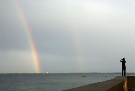 A man photographs a rainbow from the seawall in Oak Bluffs after a sudden storm. Frommer's picks: Attractions, restaurants, lodging