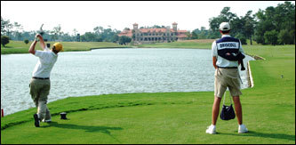 Ron Driscoll tees off on the 18th hole of the Tournament Players Club (TPC) at Sawgrass in Ponte Vedra Beach, Fla. The course's opulent new clubhouse is in the background. Brian Bateman is the caddie.