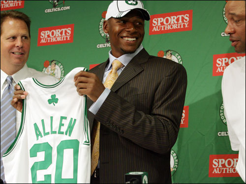 Allen holds up his No. 20 jersey as Danny Ainge, left, and head coach Doc Rivers look on.