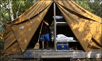 After breakfast, the boys at Pine Island Camp in Maine make their beds, sweep their tents, and tidy their trunks. Jamal DeGraffe, 12, worked on the tent he shares with four other boys; campers compete to see whose can be kept the cleanest.