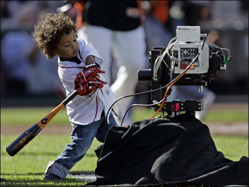 D'Angelo Ortiz plays with a bat near an on-field camera.