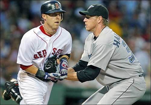Both Red Sox runner Dustin Pedroia and Toronto pitcher Roy Halladay appear to have their eyes closed as the Blue Jays starter tags out Boston's second baseman on a fourth-inning, check-swing nubber up the first-base line.