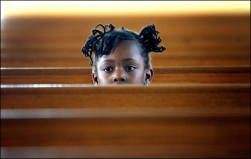 Mintou Barry, 4, of Dorchester poked her head up from the pews of the 12th Baptist Church during a Rwandan Independence. The concert was held to bring attention to the plight of children in that region of Africa.