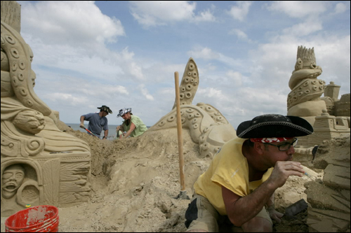 Matthew Shamaly (right) of Revere blew air to remove unwanted sand while working on a giant sculpture from the movie 'Pirates of the Caribbean' for the New England Sand Sculpting Festival, at Revere Beach on July 11.