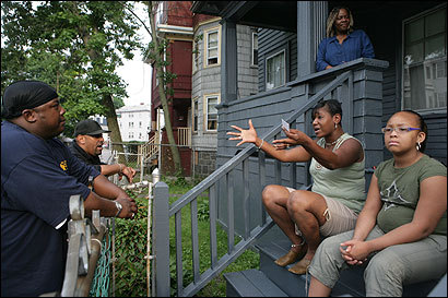 Street workers Rodney Mitchell (left) and Paul Alves spoke with Adrianne Fonfield and her daughter Jaida in Mattapan earlier this month.
