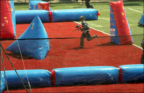 At the National Pro Paintball League competition at the Brockton Fairgrounds, a competitor ran for cover behind an inflatable piece. One hundred seventy-five teams competed in the weekend-long event.