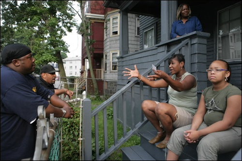 Rodney Mitchell (left) and Paul Alves, street workers for Youth Development and Family Services, talked to Adrianne Fonfield and her daughter Jaida on July 5 in Mattapan.