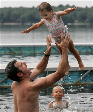 Kevin O'Rouke of Easton, tossed his daughter Olivia into the air as her twin sister, Claire, waited her turn at Massapoag Lake.