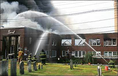 Firefighters worked to control the eight-alarm blaze yesterday at the Bernat Mill complex in Uxbridge that housed 65 businesses.