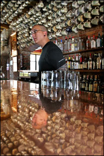 Leon Perrin mans the bar at Gritty McDuff's, where 460 beer mugs hang from the ceiling.