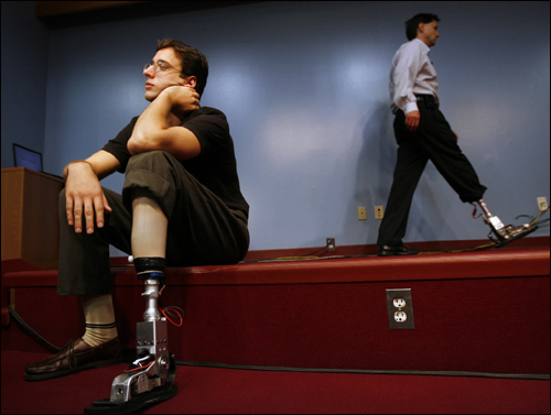 Garth Stewart (left), an Iraq war veteran, demonstrated the first powered ankle foot prosthesis prototype Monday at the Providence Veterans Affairs Medical Center. The invention was created by the Biomechatronics Group at the MIT Media Lab, headed by professor Hugh Herr (right). Herr, a double amputee, was wearing the only other prototype. The prosthesis propels users forward with tendon-like springs and an electric motor.
