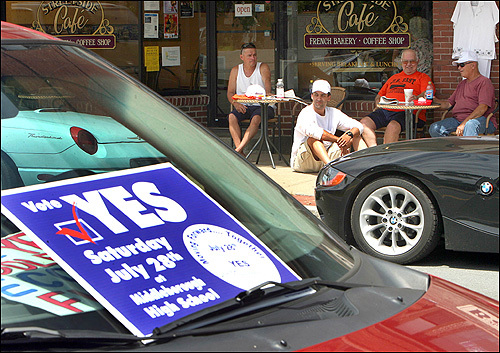 A group of men ate lunch at the Streetside Cafe in downtown Middleborough where a special town meeting was held today to vote on the building of a casino in the town. A sign in a car window proclaimed support for the vote.