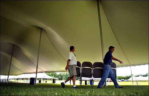 Frank Vaz, left, and David Araujo carried a set of folding chairs to arrange underneath on of four huge tents set up on the Middleborough High School athletic fields to accomodate the thousands of Middleborough voters expected to vote in today's special town meeting for a casino in the town.