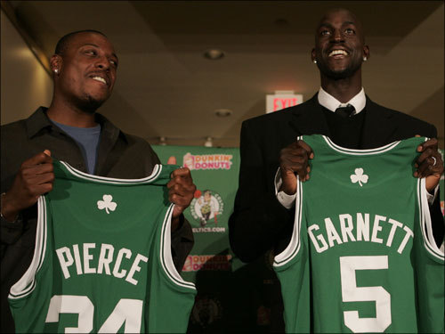 Paul Pierce, left, and newly acquired Kevin Garnett hold up their jerseys during the press conference to introduce Garnett Tuesday night at the Boston Garden.