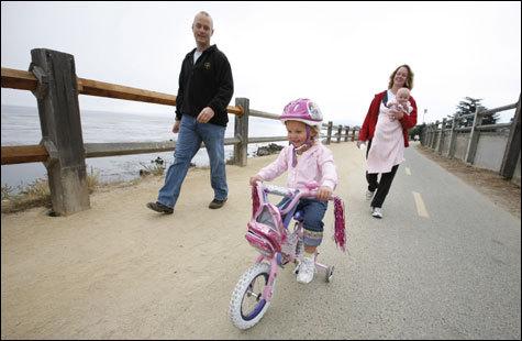Hope Eldridge, 3, cruises on her bike while parents Erik and Katie Eldridge, with 4-month-old daughter Faith, walk along the Monterey Bay Recreation Trail in Monterey, Calif.