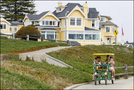 The Gelay family, from Las Vegas, ride a four-wheeled surrey in front of the Victorian-styled Seven Gables Inn on the Monterey Bay Recreation Trail.