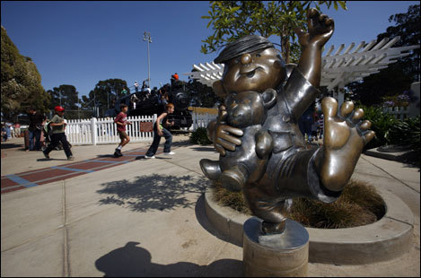 Children run past a statue of Dennis the Menace at a playground inspired by cartoonist Hank Ketcham.
